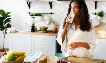 smiled-attractive-mulatto-woman-is-drinking-milk-near-table-with-fresh-fruits-white-modern-kitchen-dressed-nightwear-with-loose-hair-looking-right